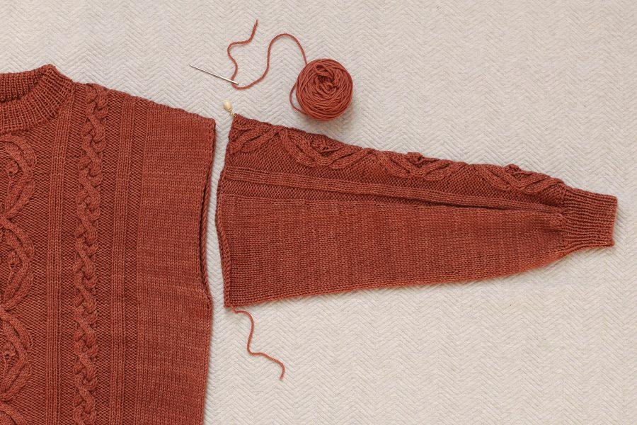 Pierwszy etap przyszywania rękawów do korpusu ręcznie dzierganego swetra