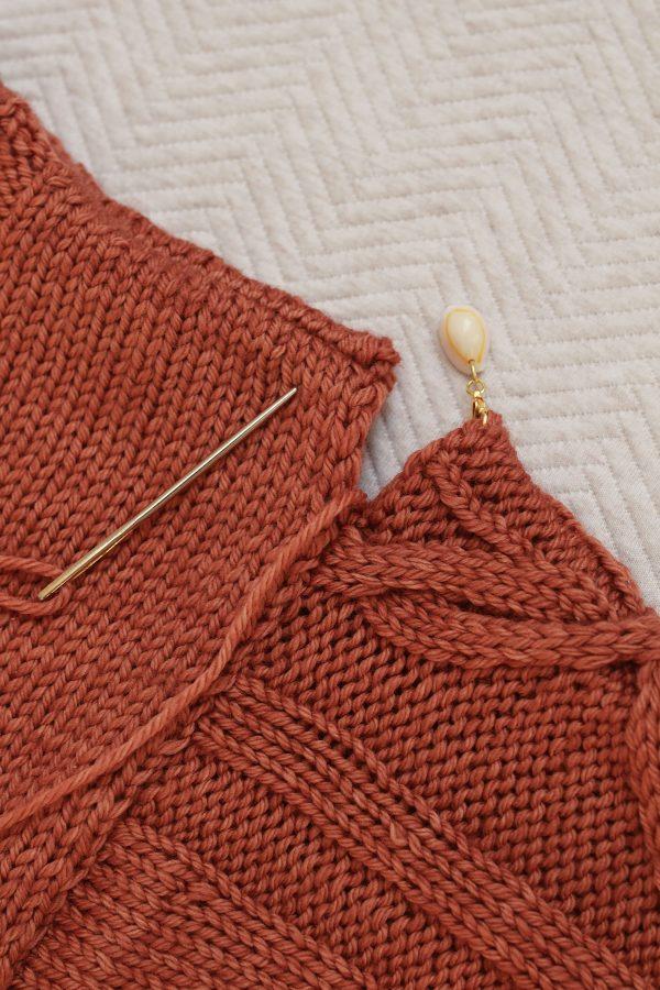 Szew powstały wzdłuż lini połączenia rękawa i korpusu w ręcznie dzierganym swetrze